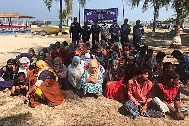 Rohingya refugees wait after their boat capsized near the Saint Martin's island in the Bay of Bengal, in Teknaf, near Cox's Bazar