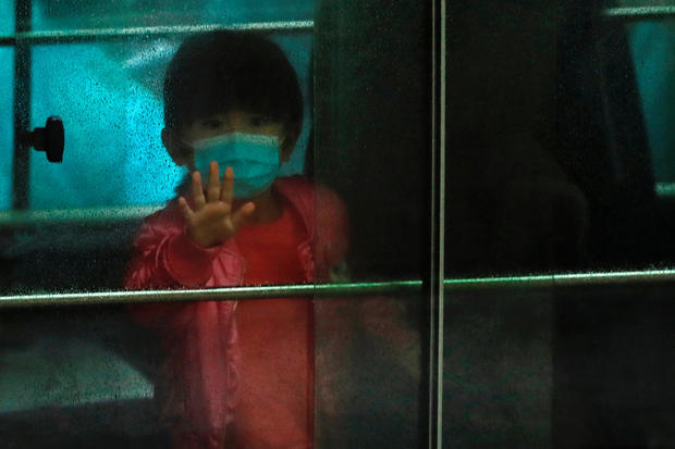 A child waves as she sits in a vehicle carrying residents evacuated from a public housing building, following the outbreak of the novel coronavirus, outside Hong Mei House, at Cheung Hong Estate in Hong Kong