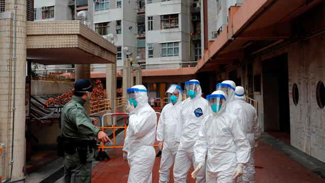 Police in protective gear wait to evacuate residents from a public housing building, following the outbreak of the novel coronavirus, in Hong Kong