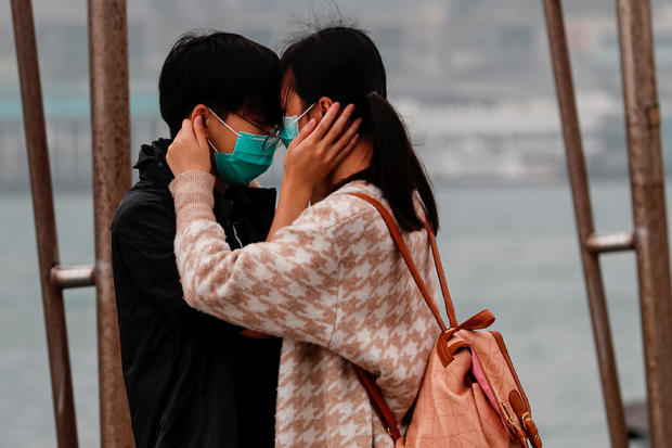 A couple wears masks as the embrace, following the outbreak of the novel coronavirus on Valentine's Day in Hong Kong