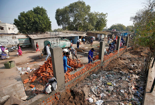 Construction workers build a wall along a slum area as part of a beautification drive along a route that President Trump and India's Prime Minister Narendra Modi will be taking during Mr. Trump's visit to Ahmedabad, India, February 13, 2020.