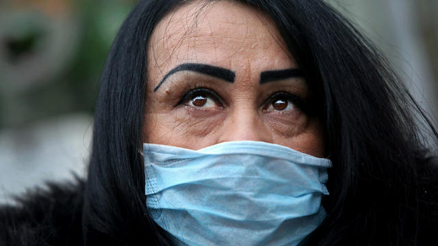 A woman wearing a face mask poses for a picture in New York City's Chinatown February 13, 2020.
