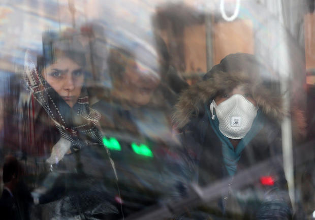 An Iranian woman wears a protective masks to prevent contracting coronavirus, as she sits in the bus in Tehran