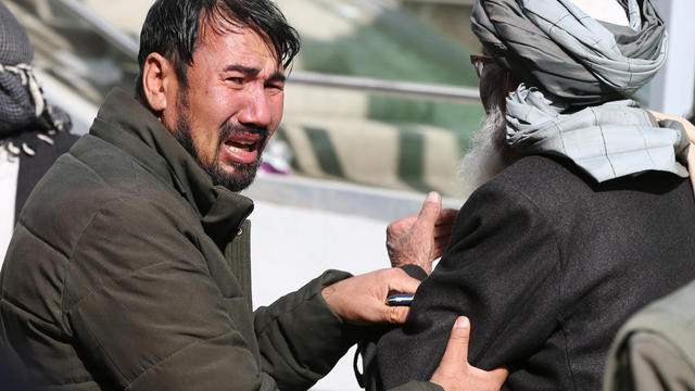Afghan men cry at a hospital after they heard that their relative was killed during an attack in Kabul