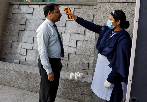 A private security guard uses an infrared thermometer to measure the temperature of a man at the entrance of a bank, following an outbreak of the coronavirus disease, in New Delhi