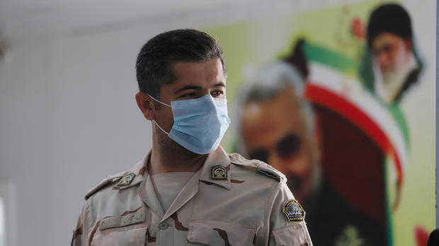 A member of Iranian Border Guards wears a protective face mask, following an outbreak of the new coronavirus, inside the Shalamcha Border Crossing, after Iraq shut a border crossing to travellers between Iraq and Iran