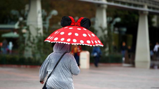 A person walks by Disneyland theme park in Anaheim