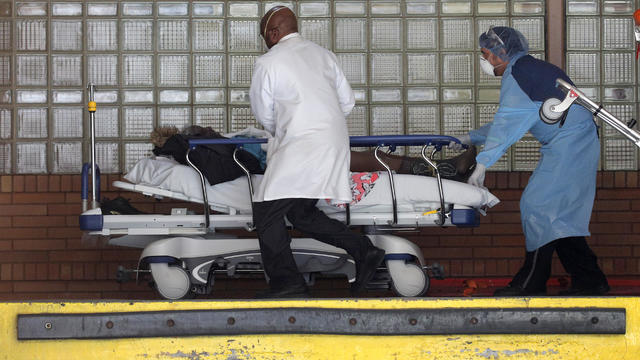 Healthcare workers rush patient on stretcher into Wyckoff Heights Medical Center during outbreak of coronavirus disease (COVID-19) in New York