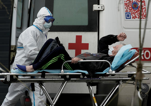 FILE PHOTO: A medical specialist wearing protective gear transports a man on a stretcher outside a hospital for patients infected with the coronavirus disease on the outskirts of Moscow
