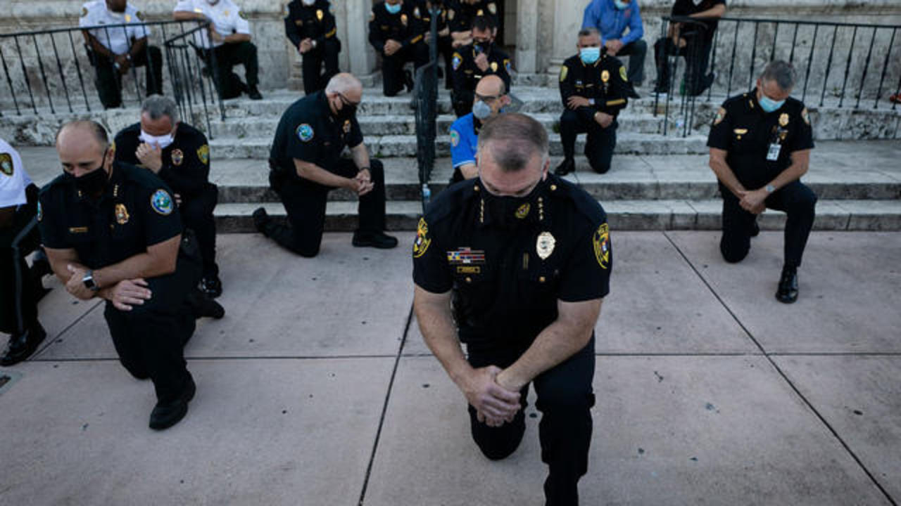 Police officers kneel and march in solidarity with protesters ...