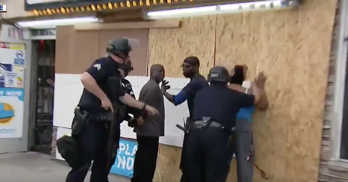 Police handcuff people trying to protect store from apparent looters, while suspects run away