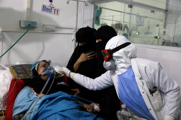 FILE PHOTO: Women watch as a nurse attends to their relative who is being treated at an intensive care unit of a hospital for the coronavirus disease (COVID-19) in Sanaa
