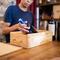 Salesman packing a wine bottle in wooden box