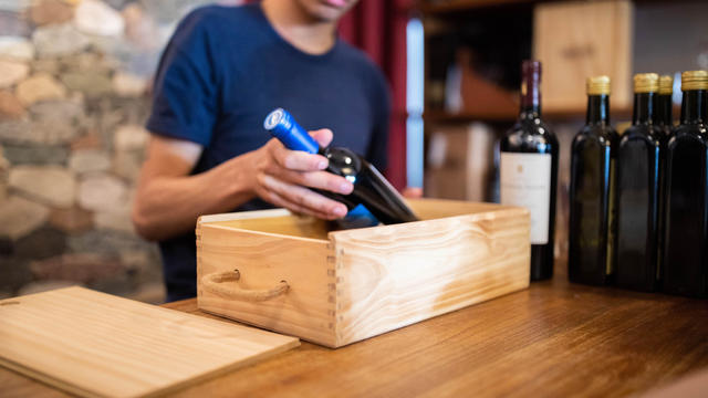 Salesman packing a wine bottle in wooden box