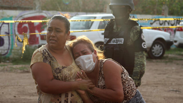 Women react outside a drug rehabilitation facility where assailants killed several people, according to Guanajuato state police, in Irapuato