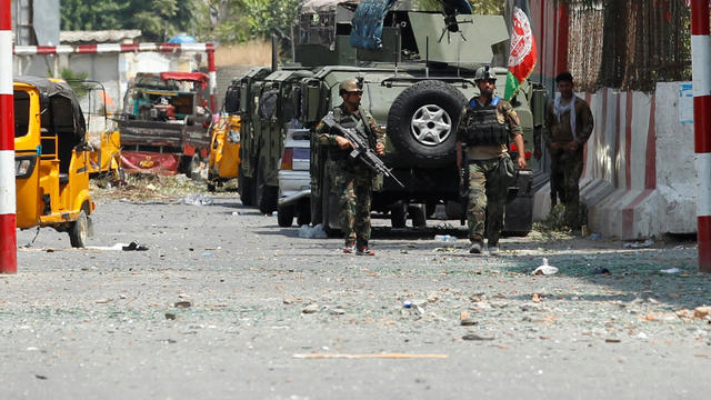 Afghan security forces keep watch in front of the site of an attack on a jail compound in Jalalabad