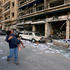 A woman carries a child as she walks past damaged shops following Tuesday's blast in Beirut