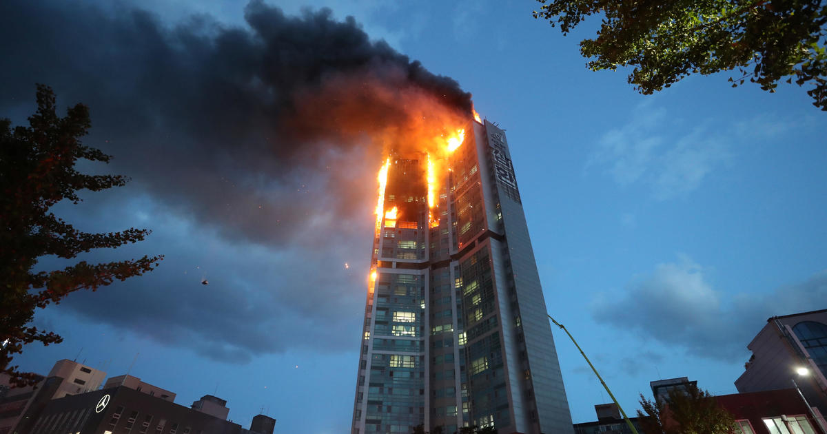 Roaring fire at top of high-rise apartment building injures scores – CBS News