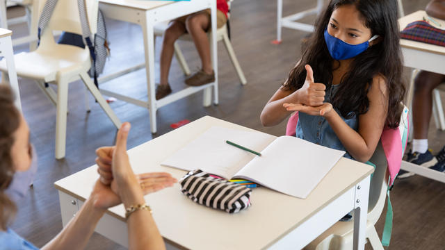Female teacher and girl wearing face masks talking to each other through sign language in class
