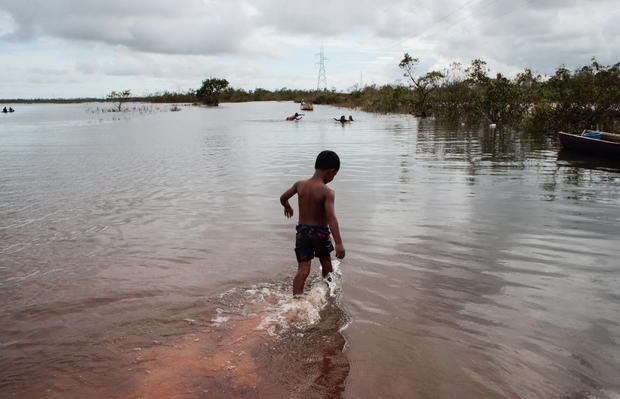 A child plays on a road flooded by the Wawa Boom river due to heavy rain caused by Hurricane Iota as it passed through the Caribbean coast in Bilwi