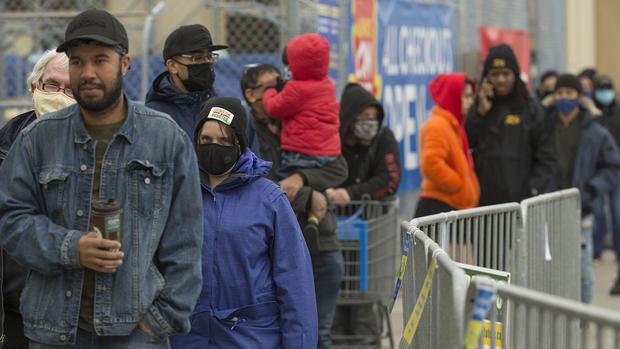 Masked customers line up outside a Walmart
