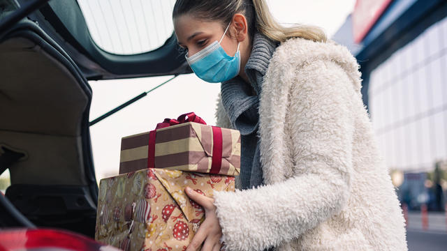 Teenage girl wears a protective mask while shopping for Christmas during COVID-19 pandemic
