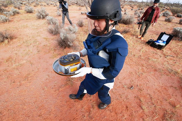 A member of JAXA collects Hayabusa2's capsule carrying the first extensive samples of an asteroid after it landed in the Woomera restricted area