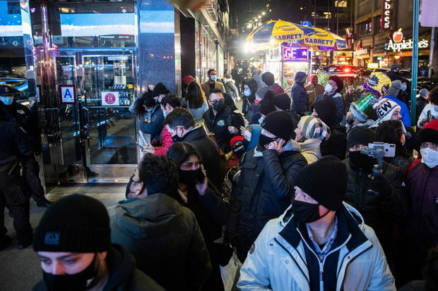 People wearing protective mask look for the Times Square ball near Times Square during the virtual New Year's Eve event following the outbreak of the coronavirus disease (COVID-19) in the Manhattan borough of New York City
