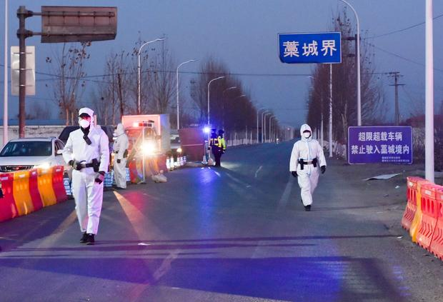 Police officers and staff members inspect vehicles at a checkpoint on the borders of Gaocheng district on a provincial highway