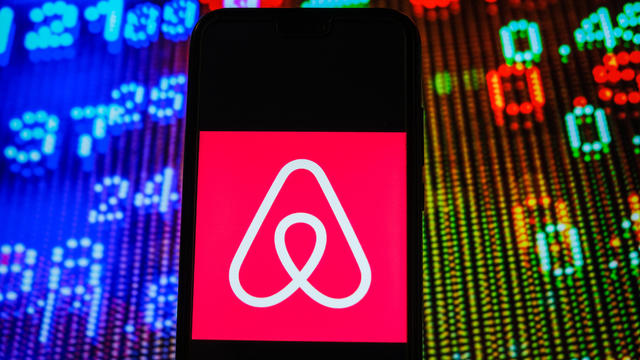 In this photo illustration, an Airbnb logo seen displayed on