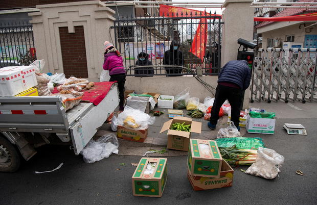 Grocery vendors sell vegetables outside a residential compound entrance in Shijiazhuang, Hebei