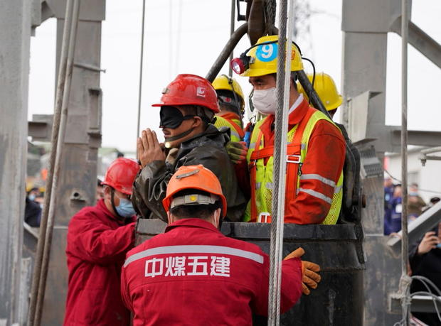 Rescue workers help a miner at the Hushan gold mine after explosion in Qixia, Shandong