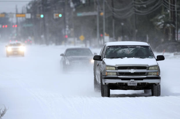 Vehicles drive on roads covered in snow and sleet February 15, 2021, in Spring, Texas.