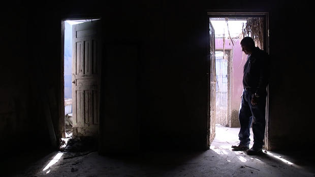 Man silhouetted in damaged home in Honduras