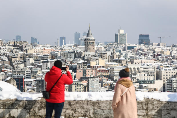 People seen taking photos in the snow-covered garden of the