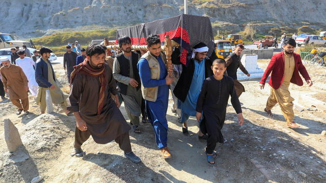 Afghan men carry the coffin of one of three female media workers who were shot and killed by unknown gunmen, in Jalalabad