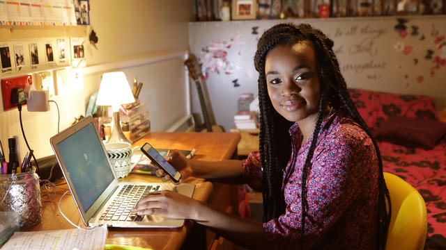 Student working at desk in bedroom at night