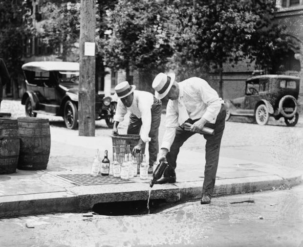 Agents Pouring liquor down a sewer on the Street