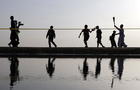 A Tokyo 2020 Olympic torch relay participant runs on a beach in Mitoyo in Kagawa Prefecture, western Japan