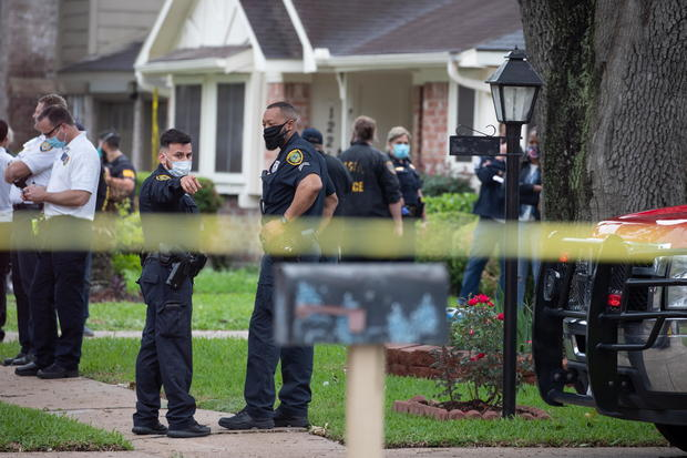 Police officials stand outside Houston residence