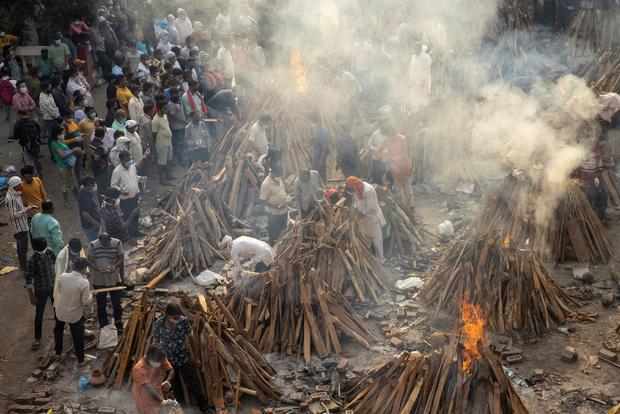 People cremate their relatives, who died due to the coronavirus disease (COVID-19), at a crematorium ground in New Delhi