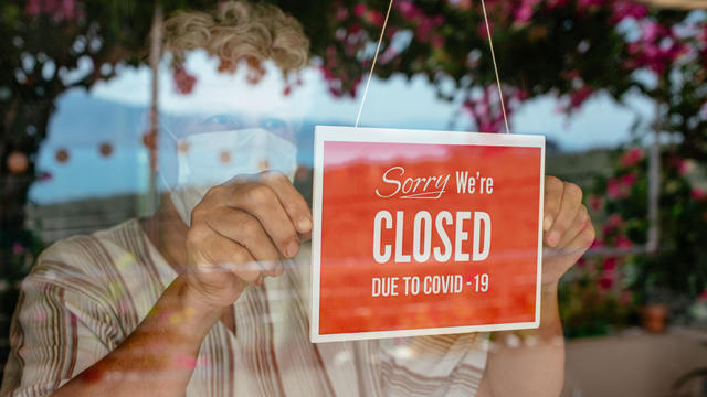Business Owner With Face Mask Putting Closed Sign