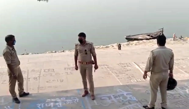 This frame grab from video provided by KK Productions shows police officials stand guard at the banks of the Ganges River, where several bodies were found, in Ghazipur district in Uttar Pradesh state, India, May 11, 2021.