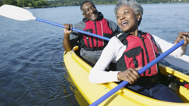 Elderly couple sitting together in a kayak on a lake