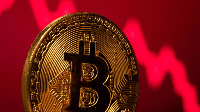 A representation of virtual currency Bitcoin is seen in front of a stock graph in this illustration