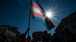 Demonstrator waving the Trans flag attends a protest where