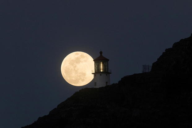 A Super Flower Moon rises over the Makapuu lighthouse in east Oahu, Honolulu