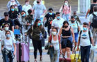 Travelers wearing protective face masks arrive at Orlando