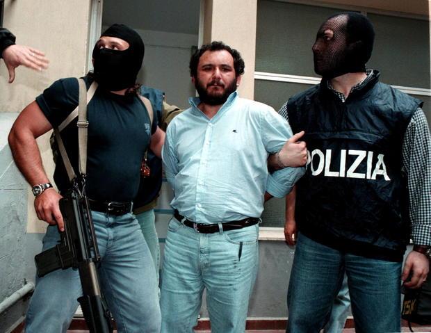 FILE PHOTO: Anti-Mafia police wearing masks to hide their identity, escort top Mafia fugitive Giovani Brusca May..