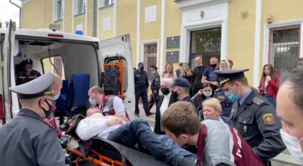 A still image taken from video footage shows Belarusian prisoner Stepan Latypov, who was arrested during a security crackdown on mass protests following a contested presidential election in 2020, being carried out of a court building after he stabbed hims